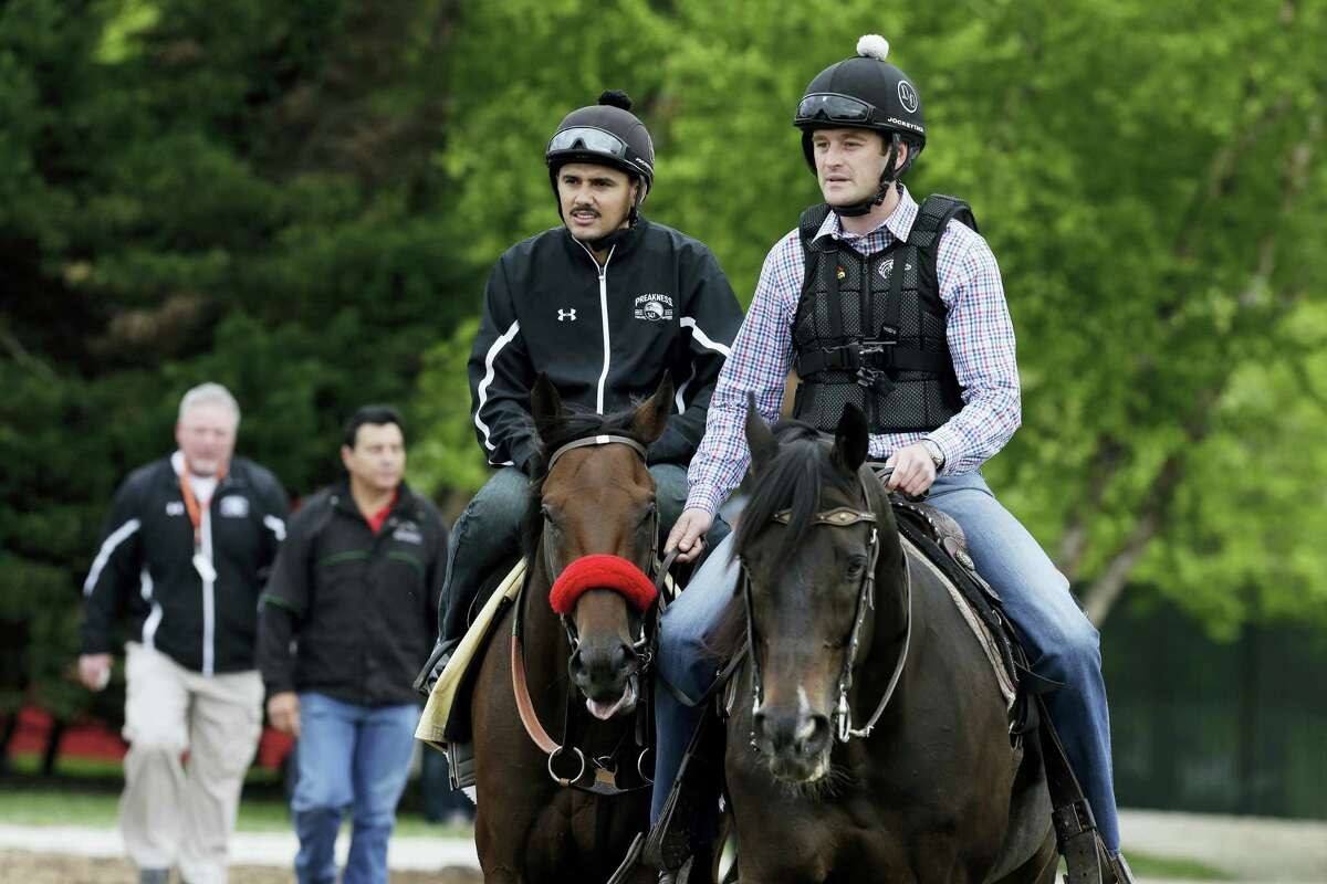 Kentucky Derby winner Nyquist, left, ridden by exercise rider Jonny Garcia, is led back to the barn following a workout by assistant trainer Jack Sisterson, right on Thursday at Pimlico Race Course in Baltimore. The 141st Preakness will be held Saturday.