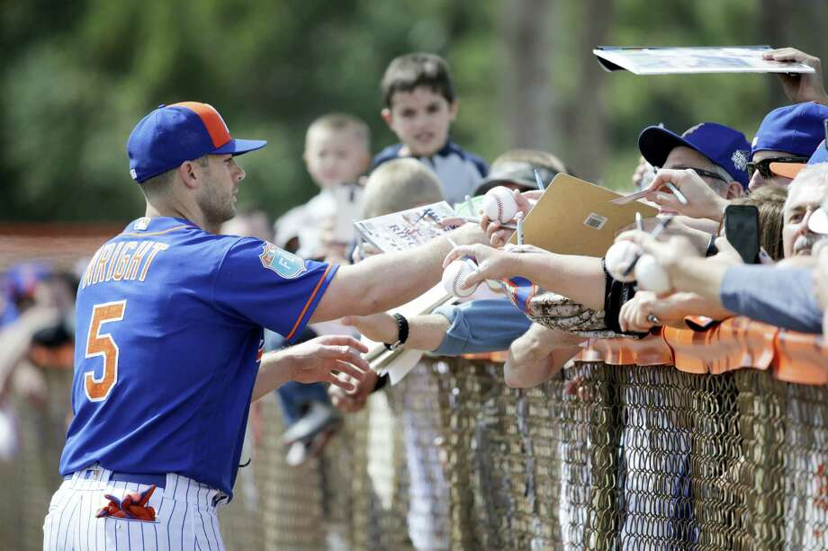 The Mets' David Wright signs autographs during spring training on Friday in Port St. Lucie, Fla. Photo: Jeff Roberson — The Associated Press   / AP
