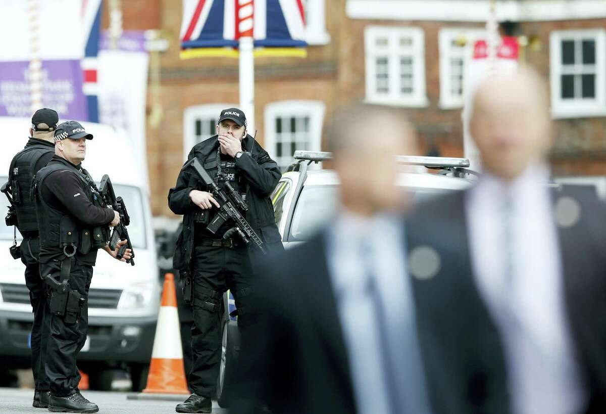 AP Photo/Alastair Grant Armed police wait at the edge of the crowd as Britain's Queen Elizabeth II does walkabout as she celebrates her 90th birthday in Windsor, England, Thursday, April, 21, 2016.