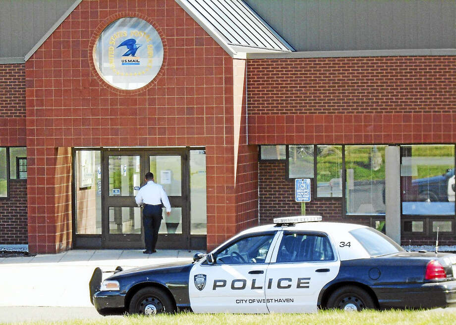 A police investigator enters the Allingtown Post Office, 75 Farwell St., Thursday morning in West Haven. The Post Office was closed and local, state and federal authorities were on scene after three men robbed the branch, one of them armed with a rifle. Photo: Wes Duplantier — New Haven Register   / Copyright 2009