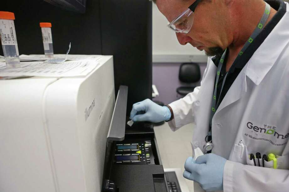 John D'Albora, 41, a senior research technician, wipes impurities from a flow cell before running it through a HiSeq X Ten machine for sequencing at the Genome Institute at Washington University on Thursday, April 23, 2015. Photo: Cristina Fletes-Boutte/St. Louis Post-Dispatch/TNS    / St. Louis Post-Dispatch