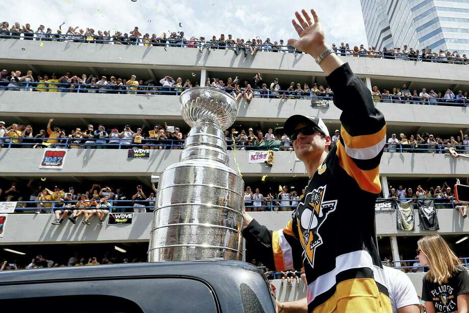 Pittsburgh Penguins' Sidney Crosby waves to the crowd while holding onto the Stanley Cup while riding along the victory parade route in Pittsburgh, Pa., Wednesday. Photo: Keith Srakocic — The Associated Press   / Copyright 2016 The Associated Press. All rights reserved. This material may not be published, broadcast, rewritten or redistribu