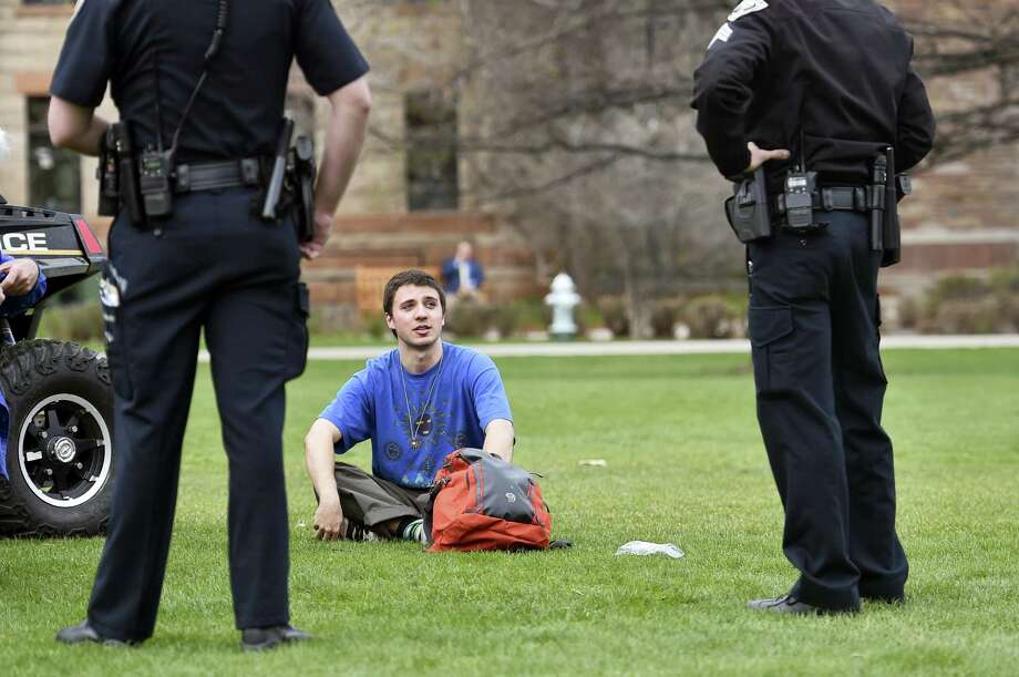 Police contact one of two men about smoking marijuana on Norlin Quad on the University of Colorado Boulder campus but ultimately did not issue any citations on April 20, 2016 in Boulder, Colo. Public consumption remains illegal under the state's recreational pot law, which was passed in 2012. Photo: Autumn Parry/Daily Camera Via AP   / Daily Camera