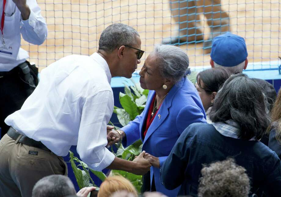President Barack Obama leans in to kiss the check of Rachel Robinson, widow of baseball hall-of-famer Jackie Robinson, before taking his seat with Cuban President Raul Castro as they attend a exhibition baseball game between the Tampa Bay Rays and the Cuban National team at the Estadio Latinoamericano Tuesday in Havana, Cuba. Photo: The Associated Press   / AP