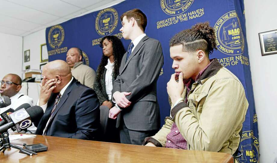 Brandon Lane, far right, son of Thomas Lane, listens to Darnell Crosland, far left, president of the Norwalk Branch of the NAACP and attorney for the Lane family, speak at a press conference at the office of the Greater New Haven NAACP in New Haven Friday. From left are Crosland; Scot X. Esdaile, president of the Connecticut NAACP; Anthony Dawson, first vice president of the Greater New Haven Branch of the NAACP; Tamara Lanier, criminal justice chairwoman of the Connecticut NAACP; David McGuire, legislative and policy director for the ACLU of Connecticut; and Lane. Photo: ARNOLD GOLD — NEW HAVEN REGISTER