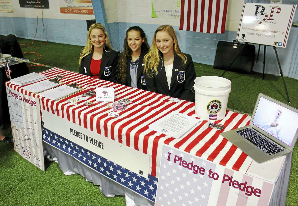 "At the Hamden Regional Chamber of Commerce's Business and Community Expo Wednesday, Brittney Stoyer, Brittney Cifarelli and Meghan Basilici, all juniors at Hamden High School and members of DECA, promote their ""Pledge2Pledge"" campaign, encouraging people to recite the Pledge of Allegiance."