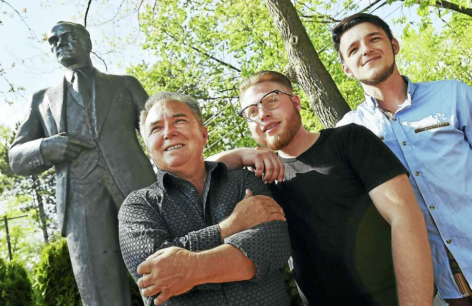 From left, Feray Gokcek of New Haven, his nephew Kubily Bayram, 21, and his son, Sansal Gokcek, 27, are seen with Gokcek's statue of Mustafa Kemal Ataturk at his city home Thursday. Photo: Catherine Avalone — New Haven Register     / New Haven RegisterThe Middletown Press