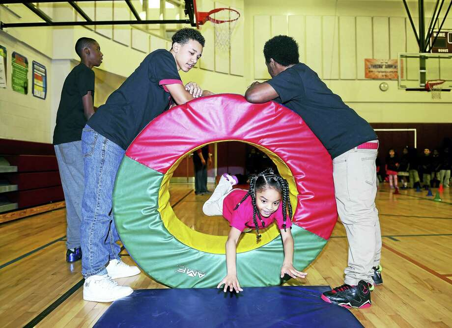 Kindergartner Arianna Smith dives through a hoop in an obstacle course set up in the gym of the Celentano Biotech Health and Medical Magnet School in New Haven Froday. Holding the hoop are Mark Shaw, left, and Devin Turner of The Hyde School of Health Sciences and Sports Medicine. Photo: ARNOLD GOLD — NEW HAVEN REGISTER