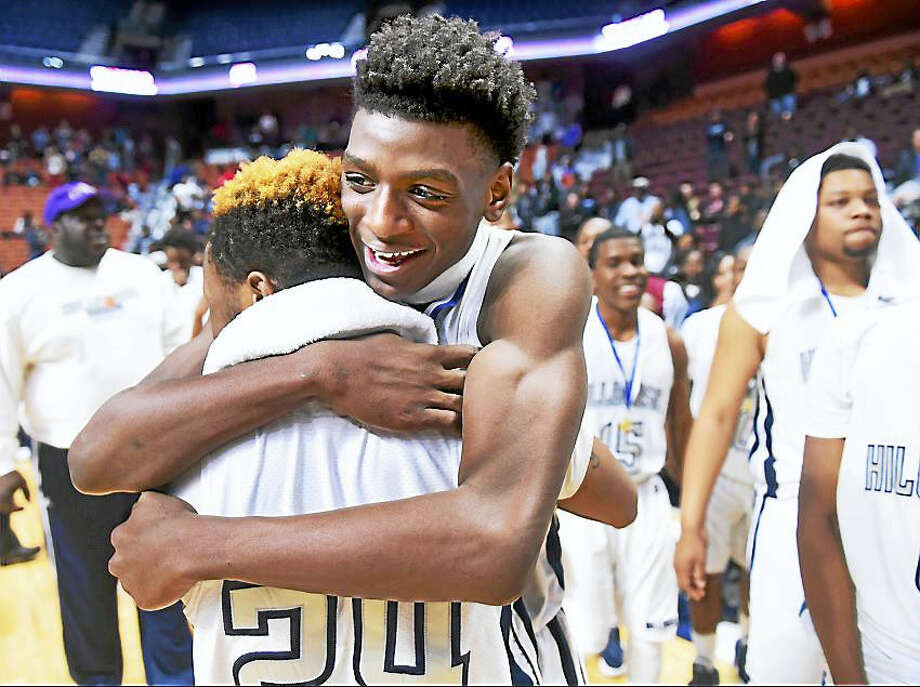 Chauness Johnson, left, and Byron Breland III, center, of Hillhouse celebrate their double overtime win this past weekend over Weaver in the Class LL Championship at the Mohegan Sun Arena. Photo: Arnold Gold — New Haven Register