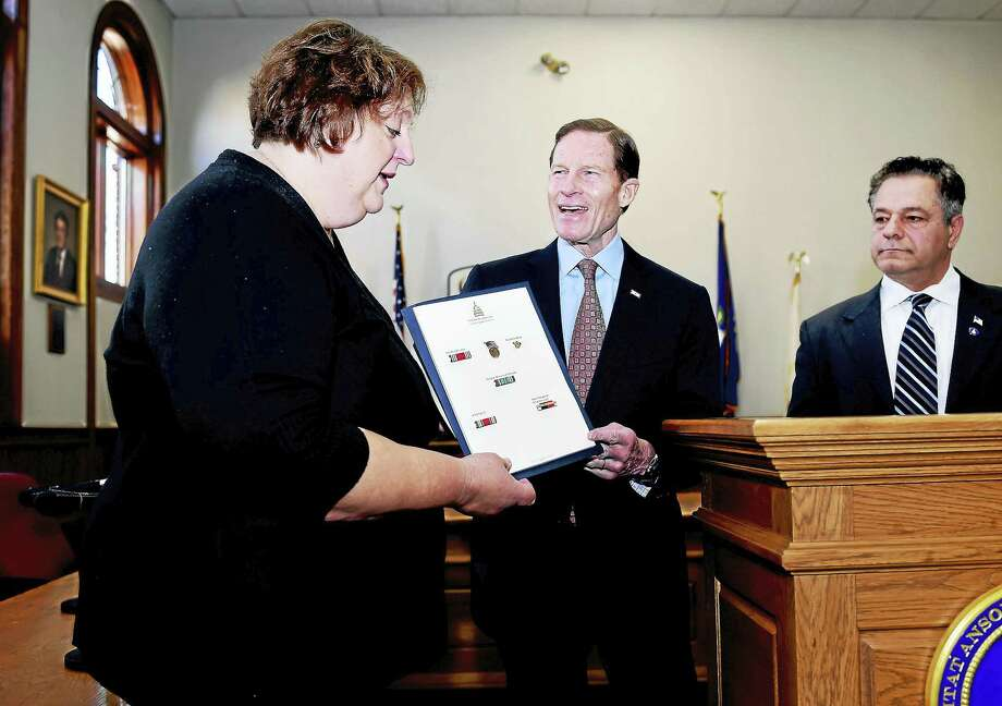 Joanne DaSilva, left, of Seymour accepts posthumous World War II medals from U.S. Sen. Richard Blumenthal on behalf of her deceased uncle, Pasquale Battaglia, at Ansonia City Hall Friday. At right is Ansonia Mayor David Cassetti. Photo: Arnold Gold — New Haven Register