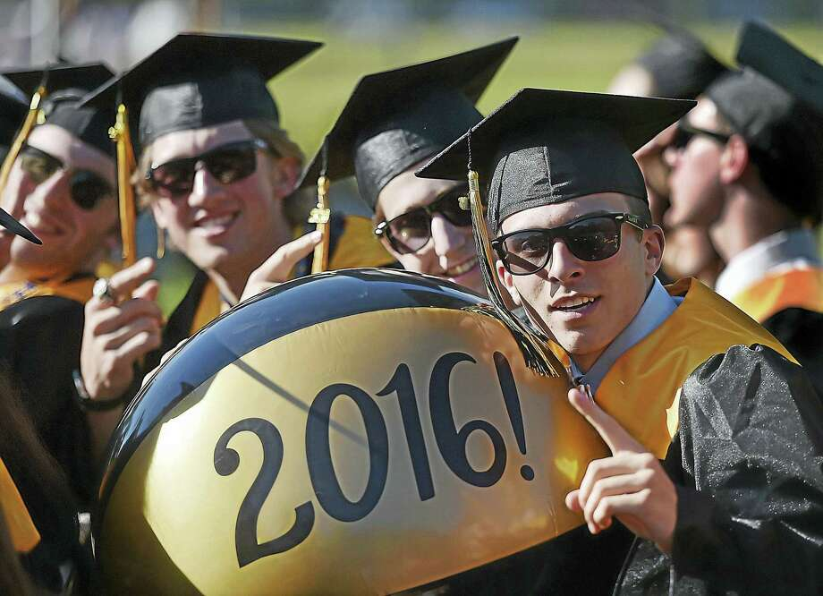 Tyler Woodward, at right, grabs the giant beach ball he and his classmates, right to left, Kerry Wolff, Christopher Winkel and Cade Williams, members of the class of 2016 at Amity Regional High School were tossing around at commencement Wednesday at the William H. Johnson Football Field. Photo: Catherine Avalone — New Haven Register   / New Haven RegisterThe Middletown Press