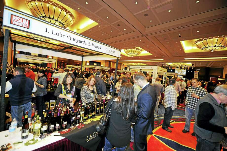 Patrons chat and sample various wines at booths during last year's Mohegan Sun WineFest. Photo: Contributed