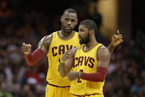 Cleveland Cavaliers' LeBron James, back, talks with Kyrie Irving in the first half of an NBA basketball game against the Orlando Magic, Saturday, Jan. 2, 2016, in Cleveland. (AP Photo/Tony Dejak)