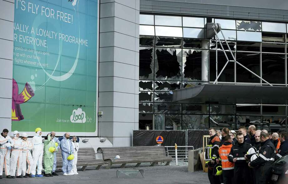 Forensic officers and firemen stand in front of the damaged terminal at Zaventem Airport in Brussels on Wednesday, March 23, 2016. Belgian authorities were searching Wednesday for a top suspect in the country's deadliest attacks in decades, as the European Union's capital awoke under guard and with limited public transport after scores were killed and injured in bombings on the Brussels airport and a subway station. Photo: AP Photo/Yorick Jansens, Pool Photo Via AP    / Belga Pool