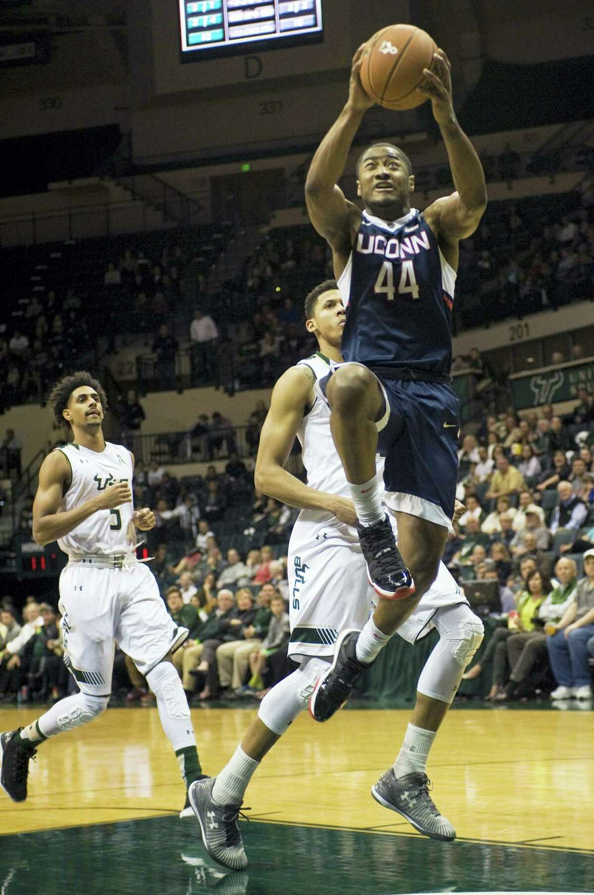 UConn's Rodney Purvis (44) scores past South Florida's Nehemias Morillo (5) and Angel Nunez, center, during the first half Thursday in Tampa, Fla.