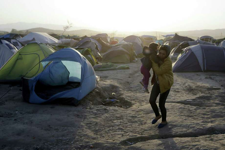 "A woman holds her baby as she walks by a tent blown by a strong wind at a camp for migrants and refugees at the northern Greek border point of Idomeni, Greece, Wednesday, April 20, 2016. Human Rights Watch says the initial round of deportations of migrants from Greece to Turkey under a new European Union-Turkey deal were ""rushed, chaotic and violated the rights of those deported."" Photo: AP Photo/Gregorio Borgia    / AP"