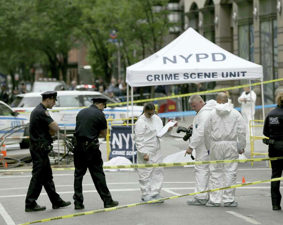 Emergency officials investigate a crime scene where a shooting took place in New York, Wednesday, May 18, 2016. Photo: AP Photo — Seth Wenig / Copyright 2016 The Associated Press. All rights reserved. This material may not be published, broadcast, rewritten or redistribu