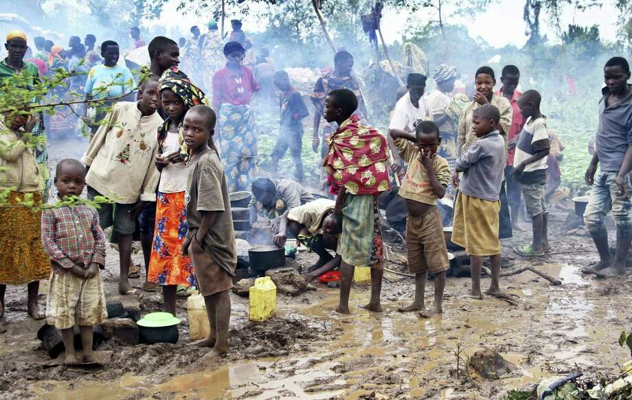 In this photo taken April 21, 2015, Burundian refugee children stand in the mud near to tents holding hundreds of other refugees who have fled from Burundi, at the Gashora refugee camp in the Bugesera district of Rwanda. More than 10,000 people from the East African nation of Burundi have crossed into neighboring Rwanda amid threats of violence ahead of elections, with many arriving saying they have been intimidated by thugs who support President Pierre Nkurunziza who may seek a third term. Photo: AP Photo/Edmund Kagire   / AP