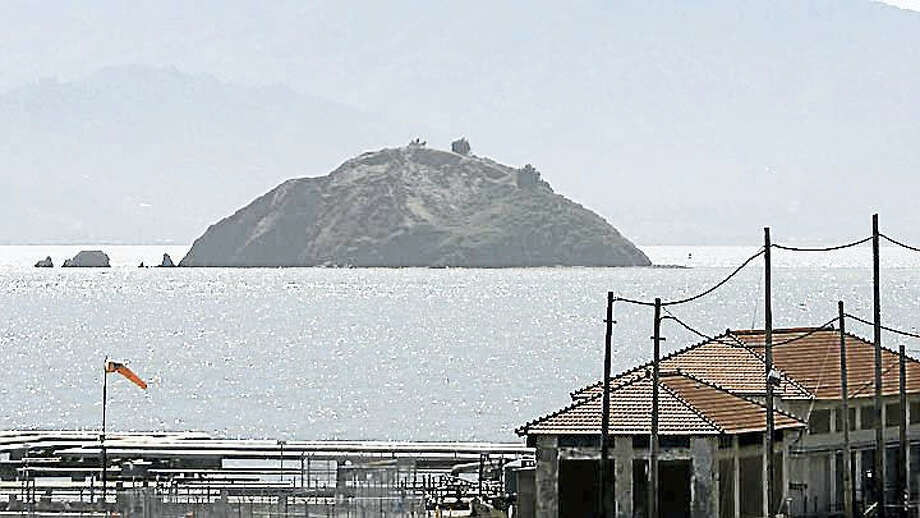 In this June 15, 2007, file photo, Red Rock Island, with Mt. Tamalpais in the background, is seen in this view taken from Point Richmond, Calif. In a city with some of the highest home prices in the county, a private island in the San Francisco Bay has had its priced slashed and is now for sale for $5 million. Red Rock, a 6-acre mass of rock, sand, vegetation and minerals, was for sale for $22 million in 2012, but then the price was slashed to $9 million without any takers. In the foreground is part of the off loading area of the Chevron oil refinery. Photo: AP Photo/Eric Risberg, File    / AP