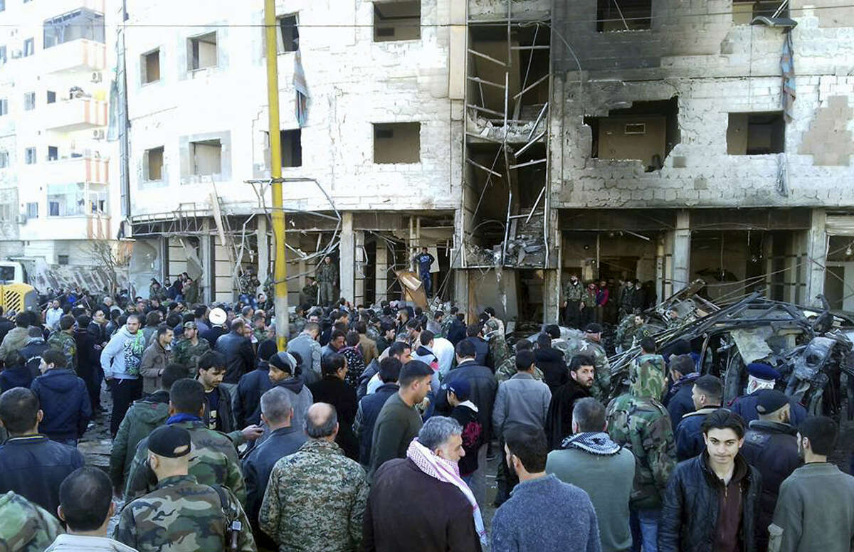 In this photo released by the Syrian official news agency SANA, Syrians gather where three bombs exploded in Sayyda Zeinab, a predominantly Shiite Muslim suburb of the Syrian capital, Syria, Sunday, Jan. 31, 2016. The triple bombing claimed by the extremist Islamic State group killed at least 45 people near the Syrian capital of Damascus on Sunday, overshadowing an already shaky start to what are meant to be indirect Syria peace talks.
