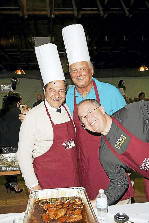 From left, Ansonia Mayor David Cassetti, Ansonia Alderman Lorie Vaccaro and Seymour First Selectman Kurt Miller at the 2014 Men Who Cook fundraiser. Photo: Contributed Photo