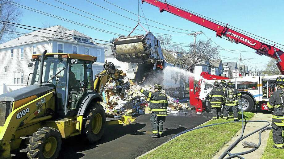 Hamden firefighters battled a fire Wednesday morning in a fully loaded recycling truck. A high-capacity wrecker had to be called in to lift up part of the truck so the burning debris could be scooped out and extinguished. Photo: Courtesy Of Hamden Fire Department