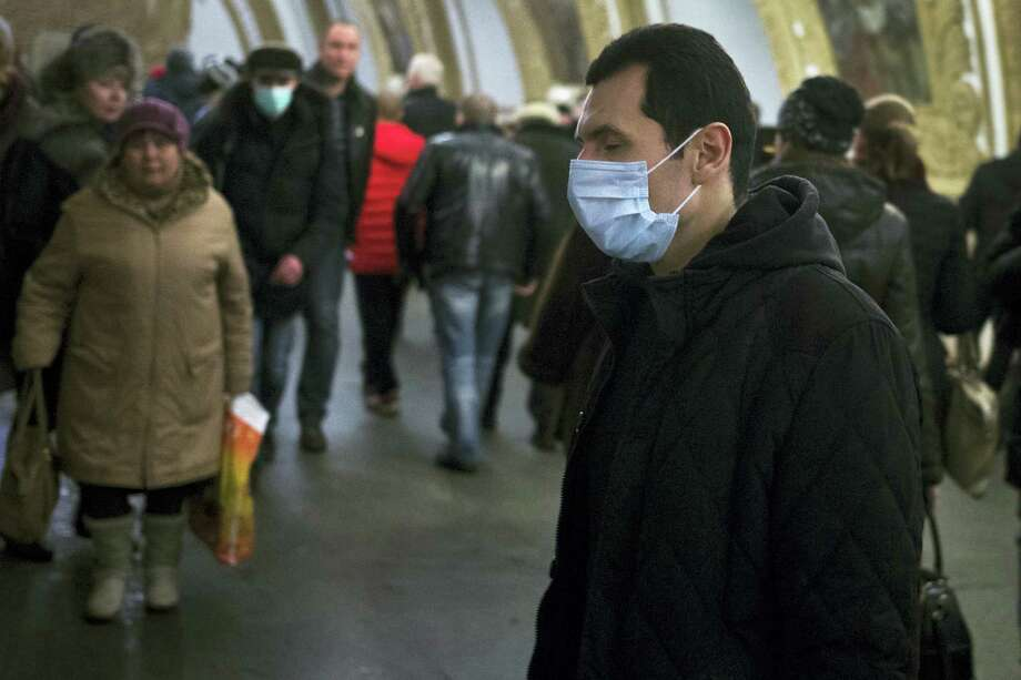 AP photo  People wearing face masks walk in a Metro station in Moscow, Russia, where flu has been a serious problem. Photo: AP / AP