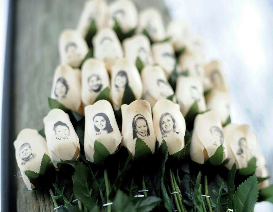 In this Jan. 14, 2013 photo, white roses with the faces of victims of the Sandy Hook Elementary School shooting are attached to a telephone pole near the school in Newtown, Conn. The deadliest shooting in U.S. history has people around the world wondering why mass violence keeps happening in America. Photo: AP Photo/Jessica Hill, File   / FR125654 AP