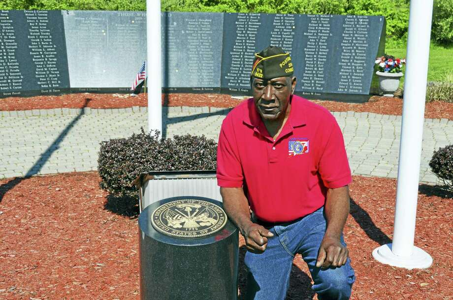 Freddy Jackson, commander of Veterans of Foreign Wars Post 9422, kneels beside the granite Army insignia marker May 11 at the Vietnam Veterans Memorial in Bradley Point Park. Photo: CONTRIBUTED PHOTO — Michael P. Walsh, City Of West Haven