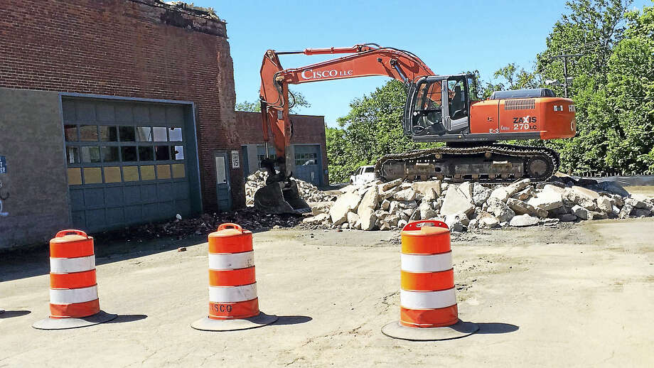 A backhoe works on tearing down part of the old CT Transit bus garage on James Street in New Haven Tuesday. Photo: LUTHER TURMELLE — NEW HAVEN REGISTER