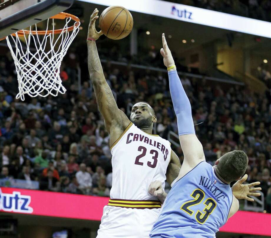 LeBron James, left, drives to the basket against the Nuggets' Jusuf Nurkic on Monday in Cleveland. Photo: The Associated Press File Photo   / AP 2016