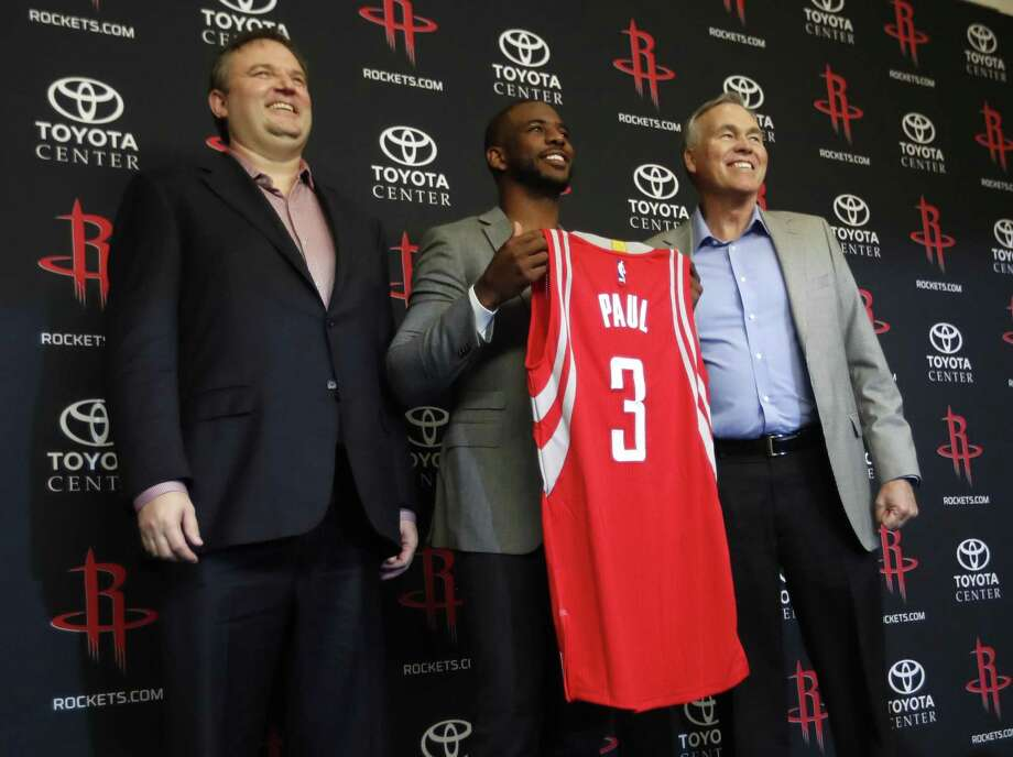 Chris Paul holds his Rockets jersey between coach Mike D'Antoni (right) and GM Daryl Morey. Photo: Karen Warren /Houston Chronicle / Internal