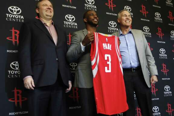 Chris Paul holds his Rockets jersey between coach Mike D'Antoni (right) and GM Daryl Morey.