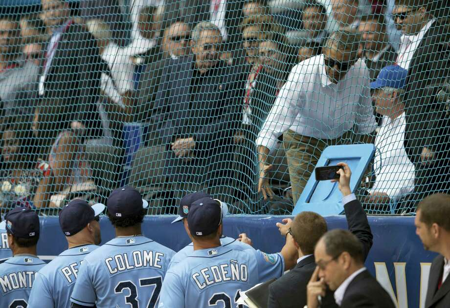Cuban President Raul Castro, center left, looks on as U.S. President Barack Obama greets the Tampa Bay Rays players before their game on Tuesday. Photo: Ismael Francisco — Cubadebate Via AP   / Cubadebate