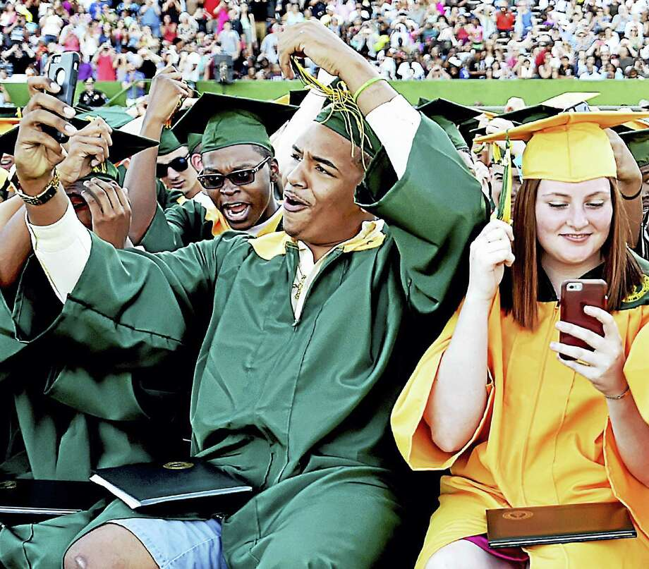 Members of Hamden High School's class of 2016 move their tassles to mark the end of commencement exercises Tuesday at Joe Bruno Field. Photo: Catherine Avalone — New Haven Register   / New Haven RegisterThe Middletown Press