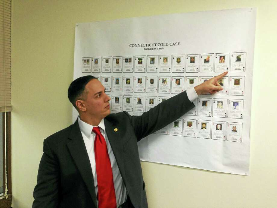 Sgt. David Zanelli points to a solved cold case on the wall in his office. Photo: Journal Register Co.