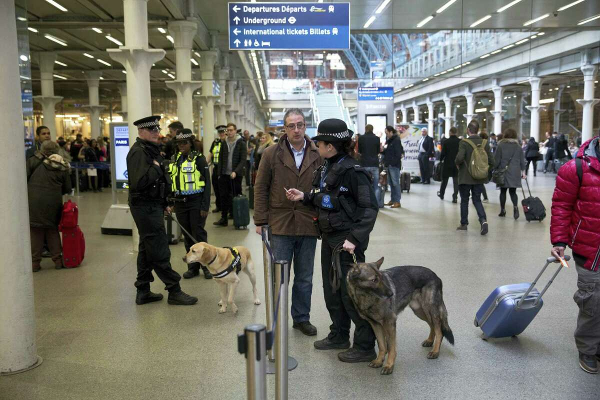 Police dog handlers speak to travelers as they patrol after Eurostar train services were suspended on the Brussels route because of the attacks in Belgium, at St Pancras international railway station in London on March 22, 2016. Explosions, at least one likely caused by a suicide bomber, rocked the Brussels airport and subway system Tuesday, prompting a lockdown of the Belgian capital and heightened security across Europe.
