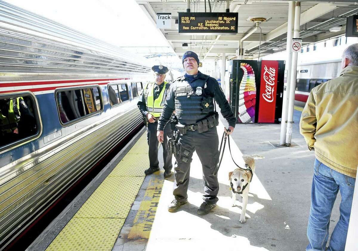 Amtrak Officer Larry Musso, left, and canine handler Joe Agnellino with explosives detection dog Roxy watch passengers board an Amtrak train heading to Washington, D.C., at Union Station in New Haven Tuesday.
