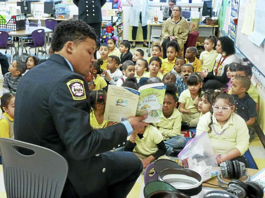Firefighter George Chin reads to kindergartners at Roberto Clemente School in New Haven. Photo: RYAN FLYNN — NEW HAVEN REGISTER