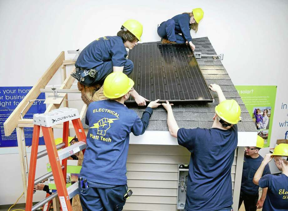 Clockwise from top right, Platt Technical High School students Jen DelBuono, Eric Marshock, Rafael Rivas and Andrew Lage install a solar panel on a new solar exhibit at the Energize Connecticut Center in North Haven Tuesday. Photo: Arnold Gold — New Haven Register