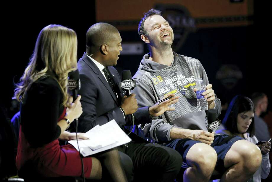 John Scott, right, laughs during a television interview during NHL All-Star game media day, Friday in Nashville, Tenn. Scott was elected as captain of the Pacific Division, though Arizona traded him to Montreal and he is now at the Canadiens' AHL affiliate in Newfoundland. Photo: Mark Humphrey — The Associated Press    / AP