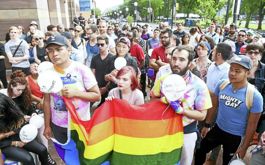 Carrying a rainbow flag, from left, Jesus Morales Sanchez, Veronica Fletcher and Elia Alessandro D'Onofrio take part in a rally in front of New Haven City Hall Monday in response to Sunday's mass shooting in Orlando, Florida. Photo: Arnold Gold — New Haven Register
