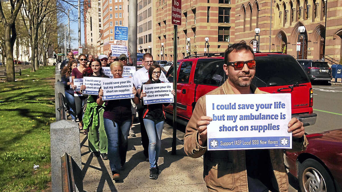 Emergency medical technicians and paramedics rally around the New Haven Green Tuesday in hopes parent company American Medical Response addresses safety concerns.
