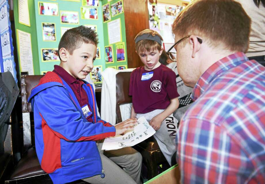 Strong School second-graders Julian Michaud, left, 8, and Jenna Kirk, center, 8, explain their science project, How Does a Controlled Environment Effect Seed Growth, to judge Noah Reynolds during the 22nd annual New Haven Science Fair at University Commons in Woolsey Hall in New Haven. Photo: Arnold Gold — New Haven Register