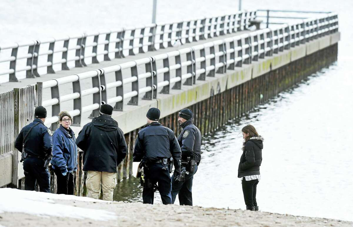 West Haven police stand where a New Haven man's body was found in the water near the Oak Street Pier in West Haven Friday.