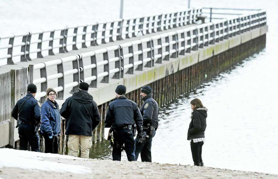 West Haven police stand where a New Haven man's body was found in the water near the Oak Street Pier in West Haven Friday. Photo: ARNOLD GOLD — NEW HAVEN REGISTER