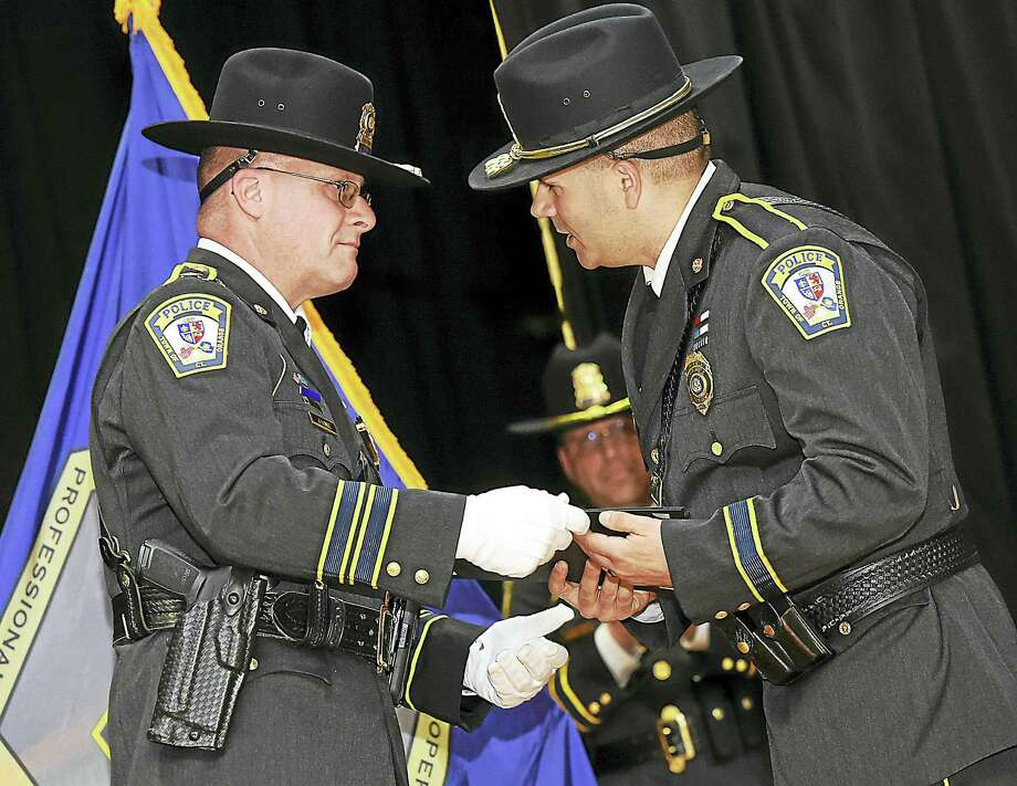 Orange police Chief Robert J. Gagne presents the lifesaving medal to Lt. Maximiano Martins at the Orange Department of Police Service awards ceremony Tuesday at the High Plains Community Center in Orange. Martins helped revive a man who collapsed at a road race in 2015. Photo: Catherine Avalone — New Haven Register   / New Haven RegisterThe Middletown Press
