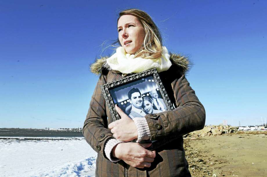Shauna Pendleton is photographed at Clinton Town Beach with a photograph of herself with her late husband, Ken, earlier this month.  It was the last photograph taken of the two. Photo: Arnold Gold-New Haven Register
