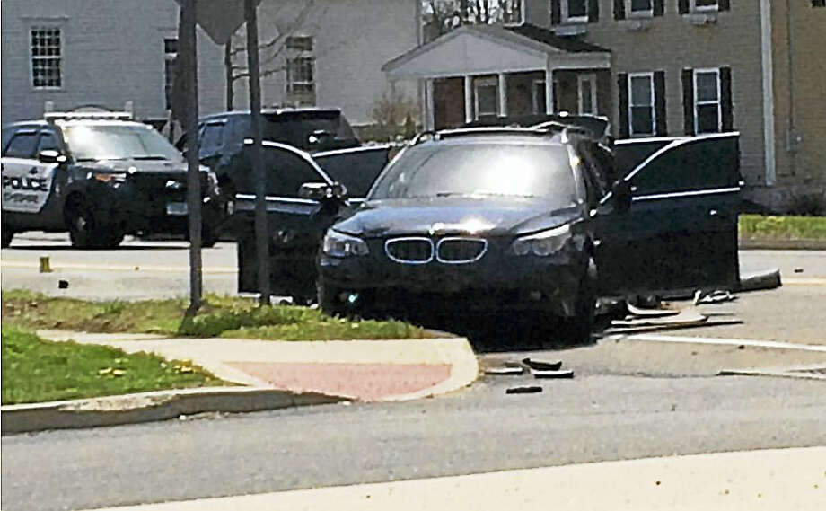 Part of Main Street in Cheshire was shut down for about four hours Monday after a BMW station wagon hit two utility poles near Maple Street. Photo: Luther Turmelle - New Haven Register