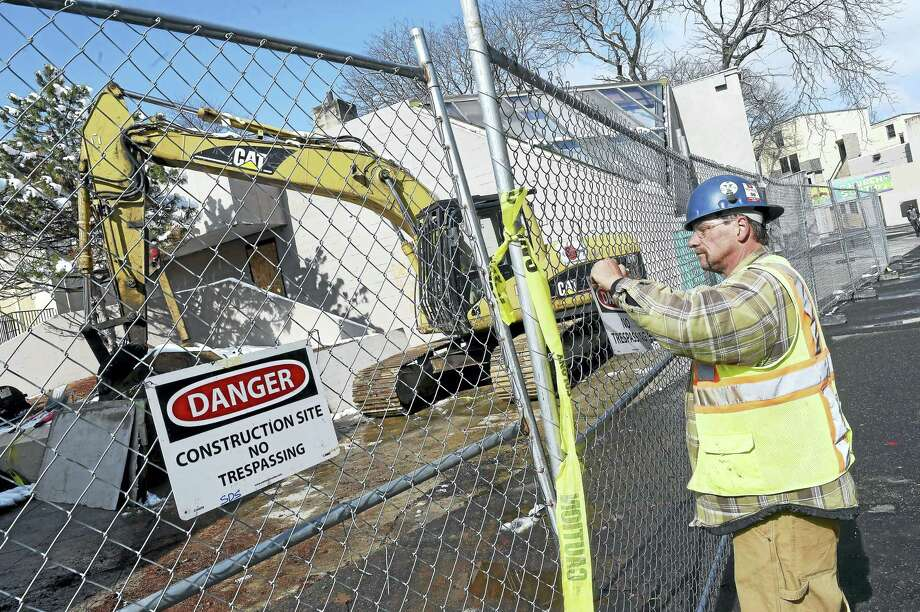 Wallace Hitchcock puts up construction signs where the first demolition takes place at Church Street South Apartments in New Haven on Monday. Photo: Arnold Gold — New Haven Register